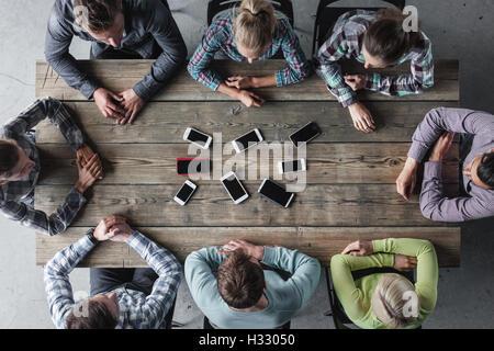 Hipster les gens assis autour de la table sans Blackberry Banque D'Images