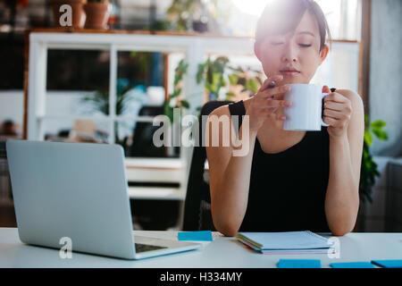 Portrait de jeune femme détendue assise à son bureau et le café. Asian business woman taking pause café au bureau. Banque D'Images