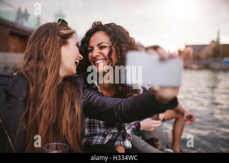Cheerful young women friends en tenant par les selfies lake. Meilleurs amis de s'amuser ensemble. Banque D'Images