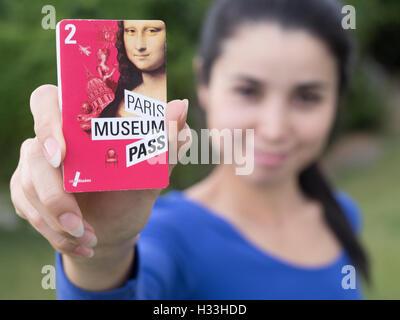 Young woman holding Paris Museum Pass 2016 Banque D'Images