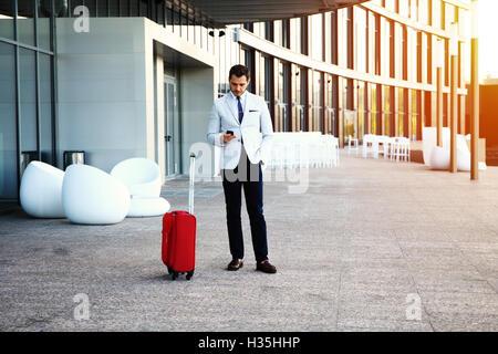 Young happy traveler businessman making appel après son arrivée à l'extérieur de l'hôtel avec ses bagages. Banque D'Images