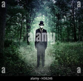 Un grand homme effrayant dans un costume noir est debout dans le bois sombre de la nuit avec du brouillard pour Banque D'Images