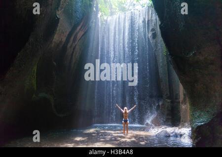 Happy woman traveler avec bras levés à profiter de la vie à une belle cascade de la forêt tropicale à Bali Banque D'Images
