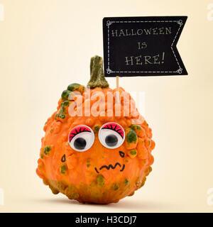 Libre d'une citrouille terrifié avec une pancarte en forme de drapeau noir avec le texte l'Halloween est ici écrit Banque D'Images