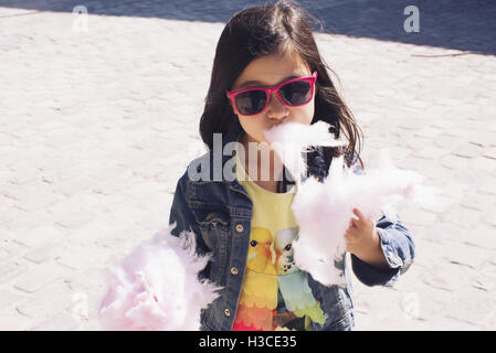 Little girl eating Cotton Candy Banque D'Images