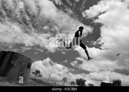 Un parkour runner effectue un saut lors d'un fonctionnement libre d'entraînement dans un parc à Kennedy, Bogotá, Banque D'Images