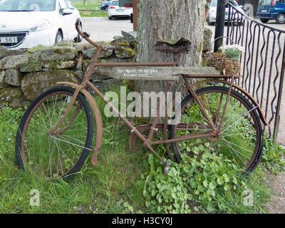 Old rusty bicyckle s'appuie contre les trois avec une jolie fleur retour Banque D'Images