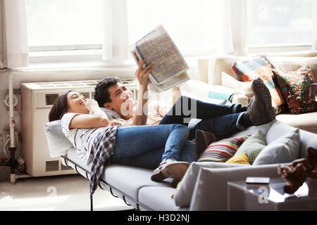 Heureux couple reading newspaper en position allongée sur un canapé à la maison Banque D'Images