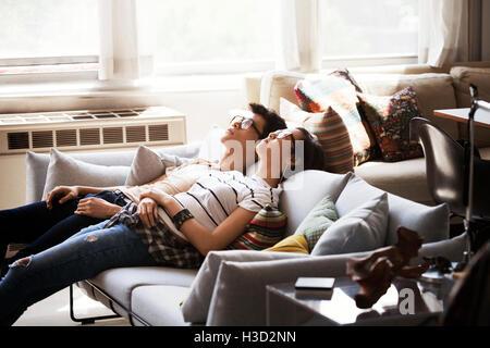Multi-ethnique détendue jeune couple reclining on sofa at home Banque D'Images