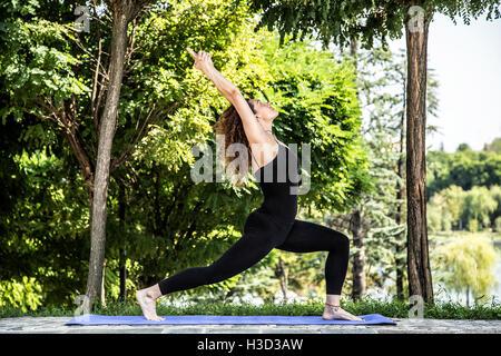 Certain woman practicing warrior pose dans park Banque D'Images