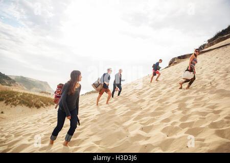 Amis marchant sur dune de sable contre le ciel Banque D'Images