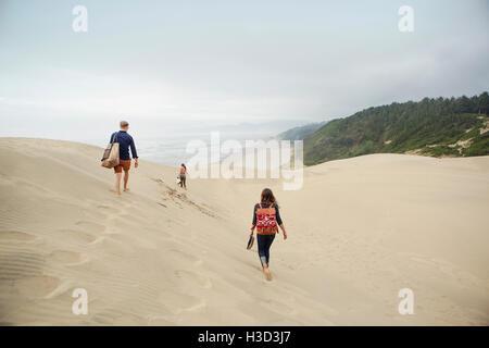 Vue arrière du friends walking on sand dune against sky Banque D'Images