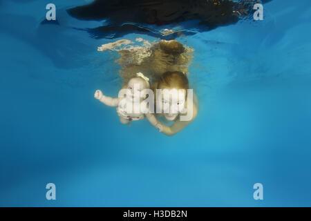 Mère avec enfant fille apprendre à nager sous l'eau en classe waterbaby dans la piscine Banque D'Images