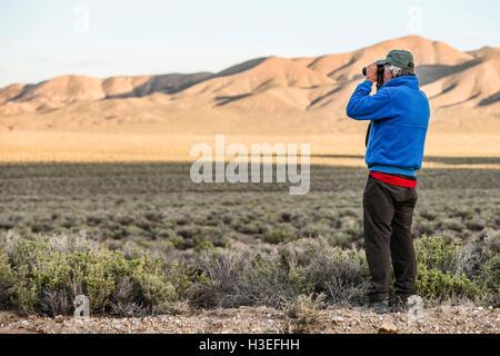 Un homme regardant à travers des jumelles. Banque D'Images