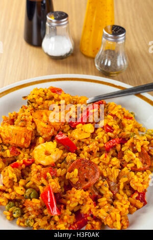 Poulet au chorizo, plaqué et paella langoustines sur une table en bois avec une sélection de condiments Banque D'Images