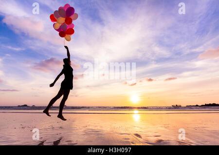 Femme dans un rêve heureux volant dans le ciel levé par ballons d'hélium Banque D'Images