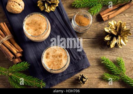 Lait de poule à la cannelle dans des verres sur fond rustique en bois avec décoration de Noël - boisson festive Banque D'Images