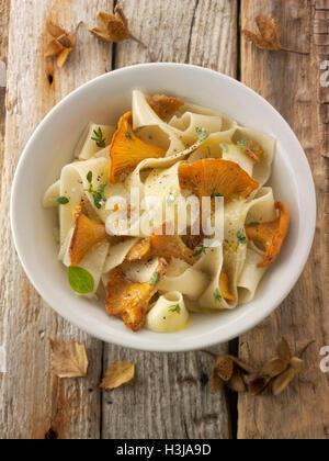 Wiild chanterelle ou girolle organiques Champignons (Cantharellus cibarius) ou sautés au beurre avec des pâtes papedelle Banque D'Images