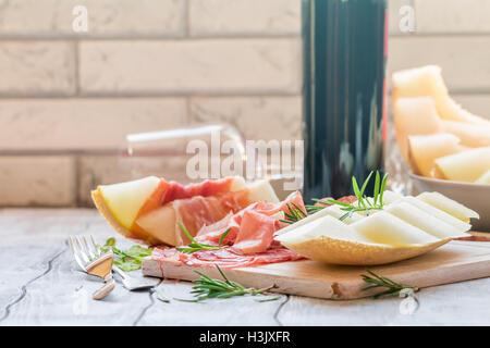 Concept de la cuisine italienne avec du vin rouge, melon et prosciutto Banque D'Images