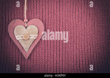 Coeur en bois sur des tricots de laine. Rustic vintage background couleur pâle vignette. Banque D'Images