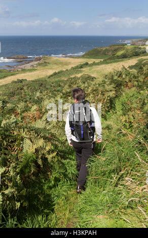 Côte d'Ayrshire, en Écosse. Vue pittoresque d'une dame Walker sur le chemin du littoral de l'Ayrshire, avec Dunure dans l'arrière-plan lointain.