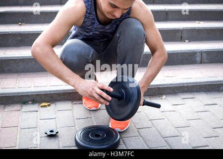 Jeune homme fintess dumbells prépare pour l'entraînement avec haltères Banque D'Images