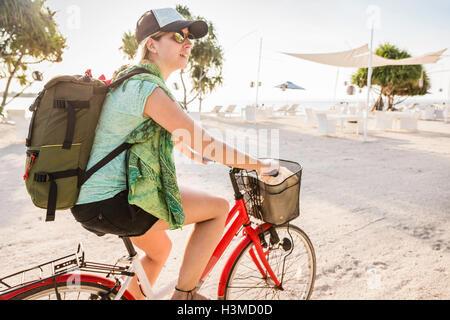 Jeune femme à vélo, sur la plage, Gili Meno, Lombok, Indonésie