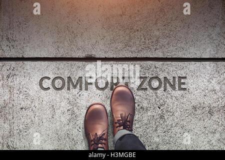 Zone de confort Concept, homme Chaussures en cuir avec étapes sur un mot: Zone de confort avec la ligne sur un sol en béton, vue d'en haut