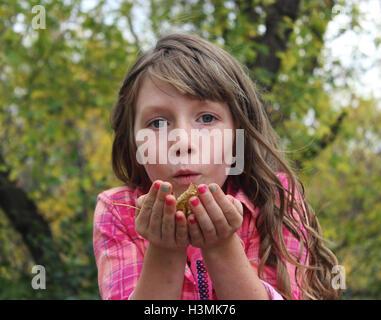 Jeune fille aux cheveux longs avec chemise à carreaux colorés et feuilles d'automne tenue leur souffle dans l'air Banque D'Images
