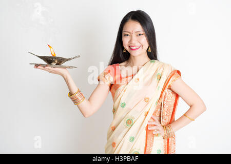 Portrait of young mixed race Indian Chinese femme en sari traditionnel robe, holding diya lampe à pétrole léger, Banque D'Images