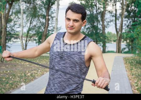 Jeune homme remise en forme avec une corde se prépare à l'exercice dans la formation à l'extérieur du parc Banque D'Images