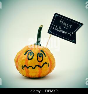 Libre d'une citrouille terrifié avec une pancarte en forme de drapeau noir avec la question Happy Halloween? Écrit Banque D'Images