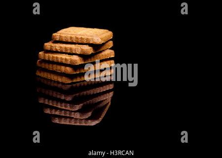 Cinq biscuits allongés sur chaque autre isolé sur fond réfléchissant noir Banque D'Images