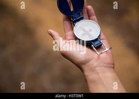 Hand holding compass in forest Banque D'Images