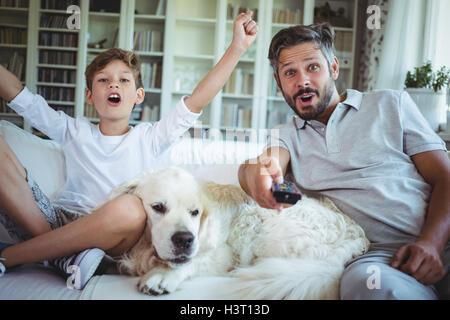 Père et fils assis sur le canapé avec le chien et de regarder la télévision Banque D'Images