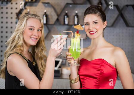 Female friends holding glass of cocktail au bar Banque D'Images