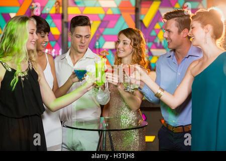 Groupe d'amis toasting verre de cocktail au bar Banque D'Images