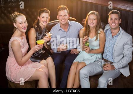 Friends holding verres de cocktail au bar Banque D'Images