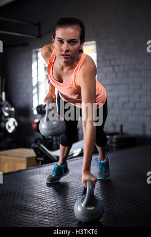 Portrait of young woman holding sportive kettlebell Banque D'Images
