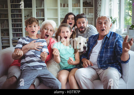 Famille heureuse à regarder la télévision dans la salle de séjour Banque D'Images