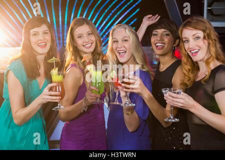 Groupe d'amis ayant verre de cocktail au comptoir du bar Banque D'Images