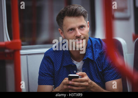 Handsome man using mobile phone in train Banque D'Images