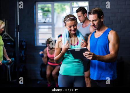 L'homme et la femme à la salle de sport à l'ordinateur de tablette Banque D'Images