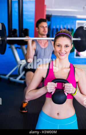 Portrait of smiling woman holding kettlebell avec man lifting weights Banque D'Images