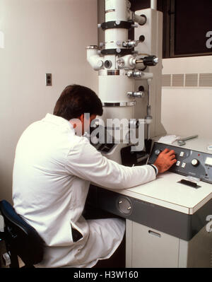 1980 MAN OPERATING MICROSCOPE ÉLECTRONIQUE À BALAYAGE Banque D'Images
