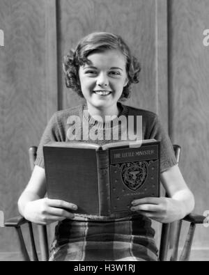 1930 SMILING TEEN GIRL READING BOOK LE PETIT MINISTRE LOOKING AT CAMERA Banque D'Images