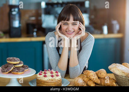 Portrait of young assis au comptoir avec sweet food on table
