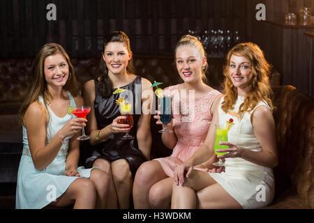 Female friends holding glasses of cocktail au bar Banque D'Images