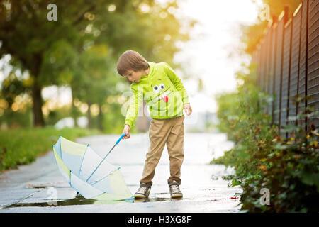 Adorable petit garçon avec parapluie dans un parc un jour de pluie, jouant et sautant, smiling, temps d'automne Banque D'Images