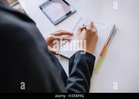 Close up shot of young businesswoman mains écrit sur le bloc-notes au bureau. Les femmes prenant des notes dans Banque D'Images